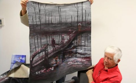 Gordon Syron showing one of his paintings of war (C) Syron